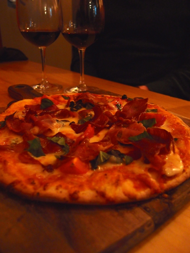 The perfect snack for a red wine - prosciutto, basil and cheese pizza